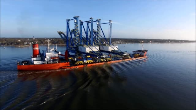 a drone captures a large ship delivering a port crane in wilmington north carolina - wilmington north carolina stock-videos und b-roll-filmmaterial