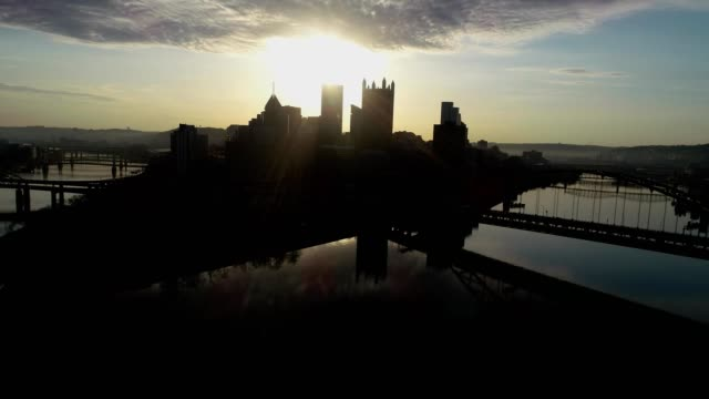 a drone captures a silhouetted view of downtown pittsburgh pennsylvania from its rivers - pittsburgh video stock e b–roll