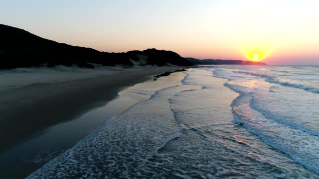 a drone captures a sunrise as it flies over a shore in east london south africa - strand south africa stock videos & royalty-free footage