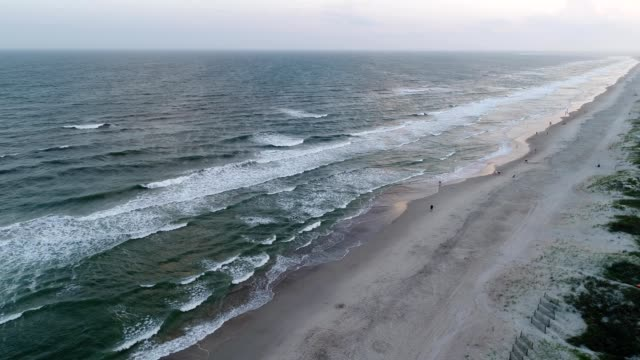 a drone captures a sunset over a beach in emerald isle north carolina - north carolina beach stock videos & royalty-free footage