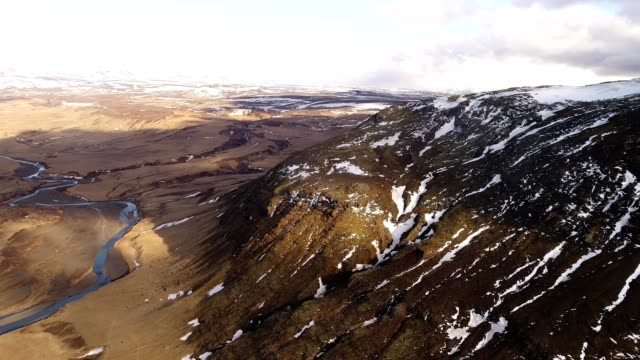 vídeos de stock, filmes e b-roll de a drone captures a volcanic mountain side in hella iceland - high dynamic range imaging
