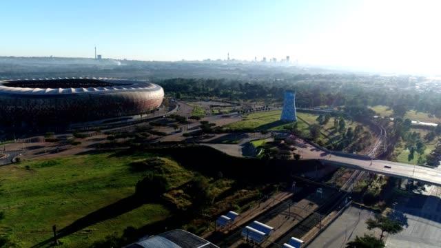 vídeos de stock e filmes b-roll de a drone captures fnb stadium in view of downtown johannesburg south africa - joanesburgo