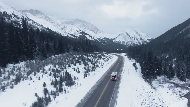 vidéos et rushes de drone captures the winter trailer journey through the forest and snow at the foot of frozen mountains in kananaskis, alberta, canada - pinacée