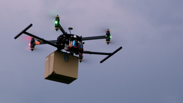 ws drone carrying a package against cloudy sky - mezzo di trasporto video stock e b–roll