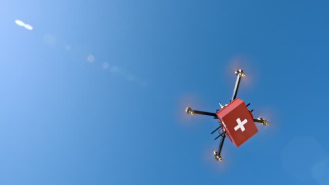 Drone carrying first aid kit in sunshine
