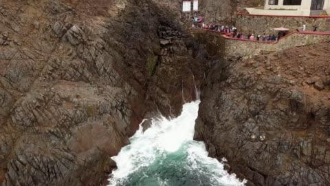 a drone clip, aerial view of the la bufadora marine geyser or blowhole in ensenada, punta banda peninsula, pacific ocean, mexico - geyser stock videos & royalty-free footage