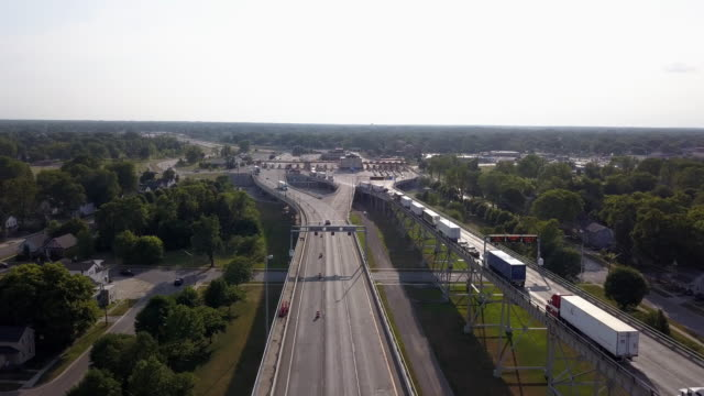drone clip looking down on a long line of semis lined up at the canadian border crossing - national border stock videos & royalty-free footage