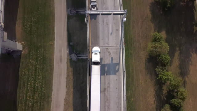 drone clip looking down on a long line of semis sweeping up to see the canadian border crossing - geographical border stock videos & royalty-free footage
