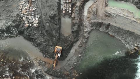 stockvideo's en b-roll-footage met drone close up van een graafmachine graven van een put in de stroom van de rivier - dam mens gemaakte bouwwerken