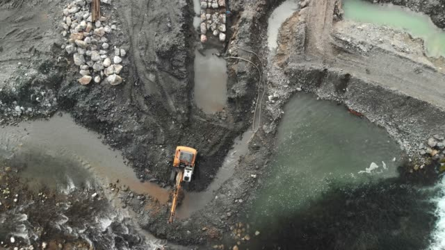drone close up of an excavator digging a pit in the river stream - crane construction machinery stock videos & royalty-free footage