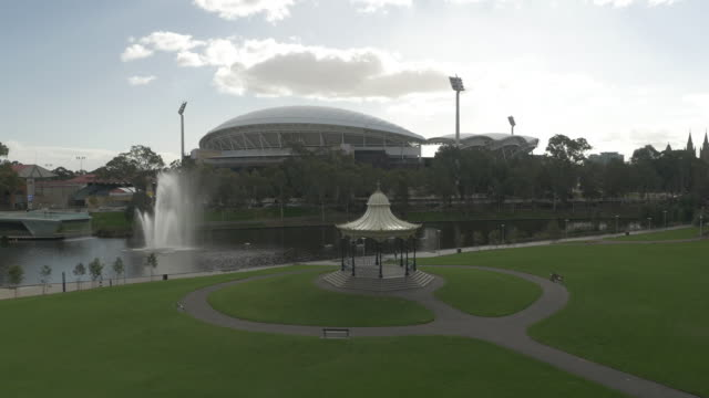 drone day - ascending over elder park rotunda, torrens river and fountain to aerial empty adelaide oval - adelaide river stock videos & royalty-free footage