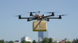 CLOSE UP: UAV drone delivery delivering big brown post package into urban city