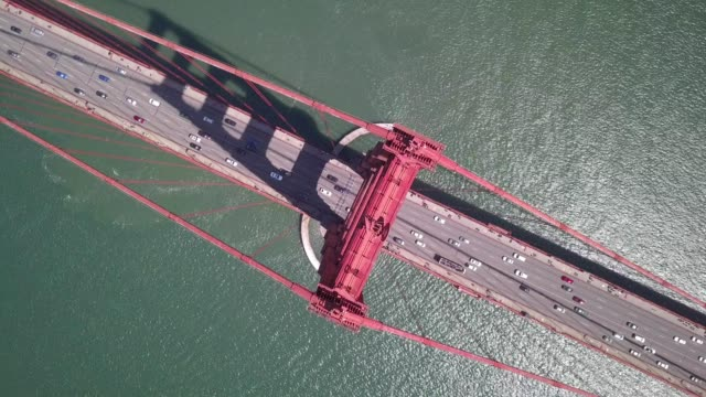 vídeos de stock, filmes e b-roll de a drone desends rotating birds eye onto the golden gate bridge in san francisco california - golden gate bridge