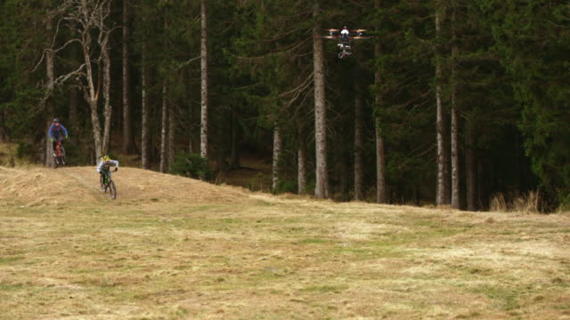 SLO MO Drone filming bikers riding through the forest