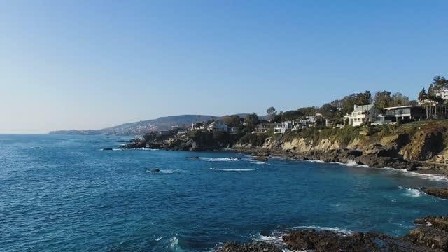 drone filming pacific ocean white waves, aerial footage of surroundings of laguna beach, california, usa, - laguna beach california stock videos & royalty-free footage