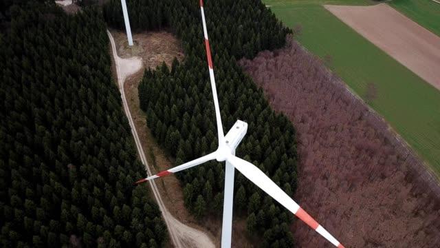 a drone films a wind turbine in morbach germany - windenergie stock-videos und b-roll-filmmaterial