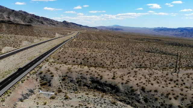 a drone flies along a highway outside the boulder dam and hoover dam area in arizona - hoover staudamm stock-videos und b-roll-filmmaterial