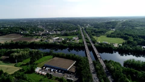a drone flies along a highway over river in hiverhill massachusetts - massachusetts stock videos & royalty-free footage