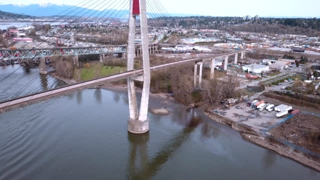a drone flies along a narrow suspension bridge and light rail train in surrey canada - bc stock videos & royalty-free footage