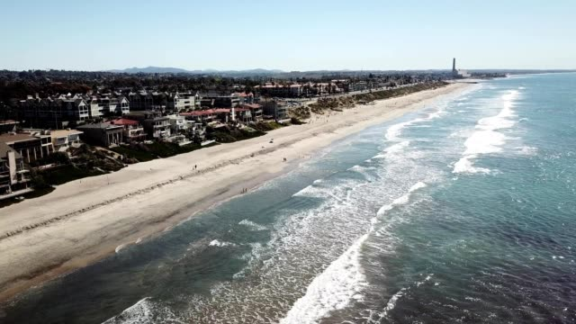 a drone flies along carlsbad beach in san diego california - carlsbad california stock videos & royalty-free footage