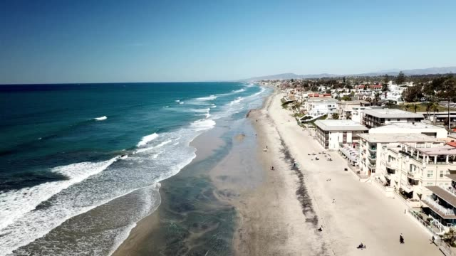 A drone flies along Carlsbad Beach in San Diego California