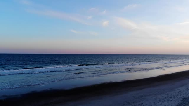 a drone flies along the beach of emerald isle north carolina - carolina beach stock videos & royalty-free footage