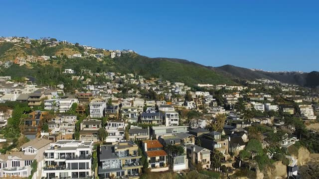 drone flies at high altitude to the coastal american town, aerial shot of pacific coast at laguna beach, california, usa - laguna beach california stock-videos und b-roll-filmmaterial