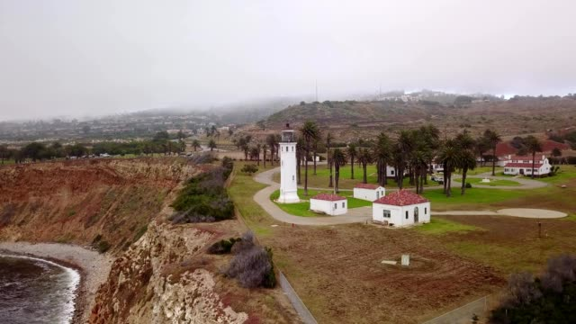 a drone flies away from a lighthouse towards the ocean in point vicente rancho palos verdes california - palos verdes stock videos & royalty-free footage