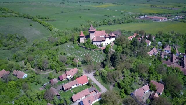A drone flies away from the fortified church of Viscri in Județul Brașov Romania
