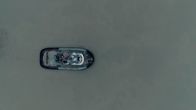 A drone flies birdseye over a tugboat on a river in Delta Canada