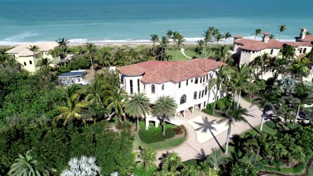 a drone flies by a beachfront mansion in jensen beach florida - stately home stock videos & royalty-free footage