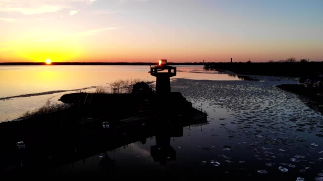 a drone flies by a silhouetted observation tower during sunset at erie basin marina in buffalo new york - lago erie video stock e b–roll