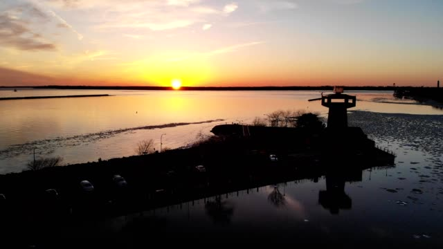 a drone flies by a silhouetted observation tower during sunset at erie basin marina in buffalo new york - buffalo new york state stock videos & royalty-free footage
