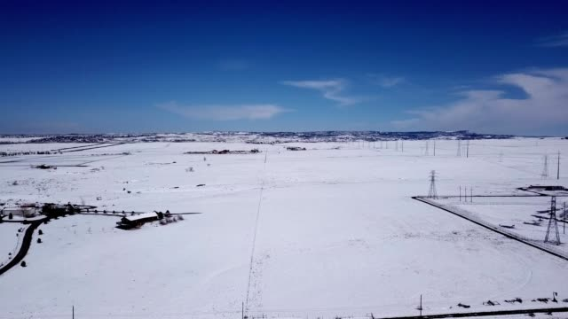 A drone flies by a snow covered ranch in Littleton Colorado