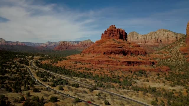 a drone flies by bell rock and route 179 in sedona arizona - sedona stock videos & royalty-free footage