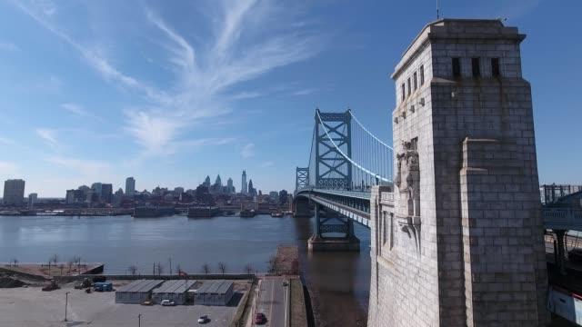 vídeos y material grabado en eventos de stock de a drone flies by ben franklin bridge from camden new jersey to philadelphia pennsylvania - benjamín franklin