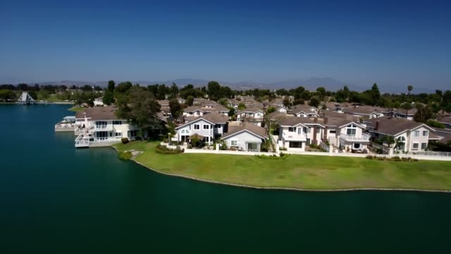 A drone flies by lake front homes in Irvine California