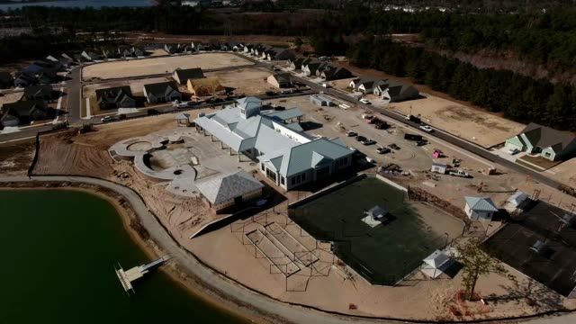 vídeos de stock, filmes e b-roll de a drone flies by the construction of a clubhouse and new neighborhood in wilmington north carolina - wilmington carolina do norte