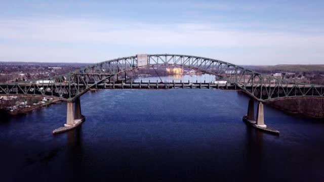 a drone flies by the delaware river turnpike toll bridge i-276 in burlington new jersey - デラウェア川点の映像素材/bロール