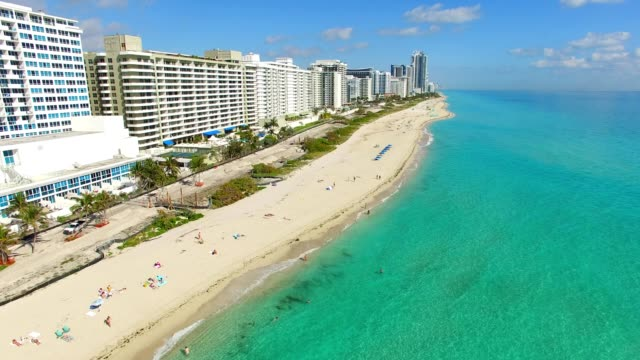 a drone flies down miami beach florida - マイアミ点の映像素材/bロール