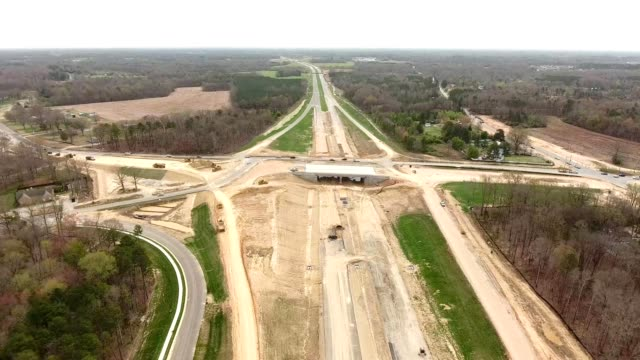 a drone flies near an interchange being constructed near charlotte north carolina - paving stone stock videos and b-roll footage