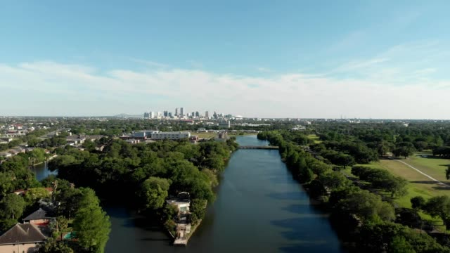 a drone flies over a bayou in view of downtown new orleans louisiana - new orleans stock-videos und b-roll-filmmaterial