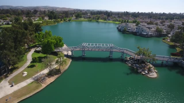 A drone flies over a bridge at Irvine Woodbridge Community in California