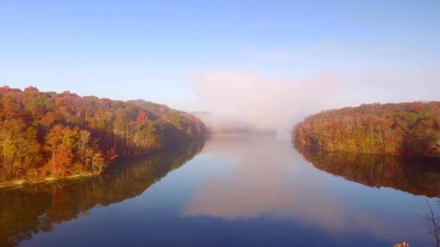 vídeos de stock, filmes e b-roll de a drone flies over a cloud covered lake with fall colors in bloomington indiana - bloomington indiana