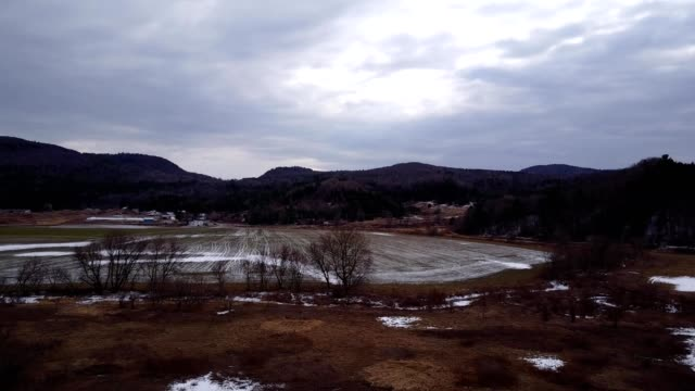 a drone flies over a farm during winter in bolton vermont - vermont stock-videos und b-roll-filmmaterial