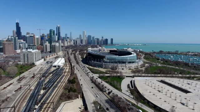 A drone flies over a highway by a stadium outside downtown Chicago Illinois