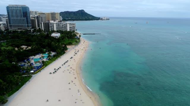 a drone flies over a hotel beach in honolulu hawaii - honolulu stock videos and b-roll footage