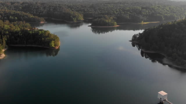 a drone flies over a lake at sunset in hot springs arkansas - arkansas stock videos & royalty-free footage