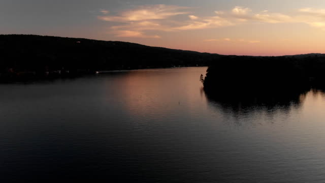 a drone flies over a lake during sunset in hot springs arkansas - arkansas stock videos & royalty-free footage
