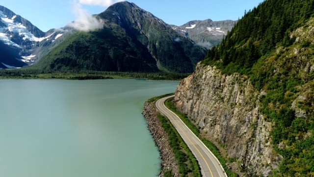 a drone flies over a lake size mountain road in anchorage alaska - anchorage alaska stock videos & royalty-free footage